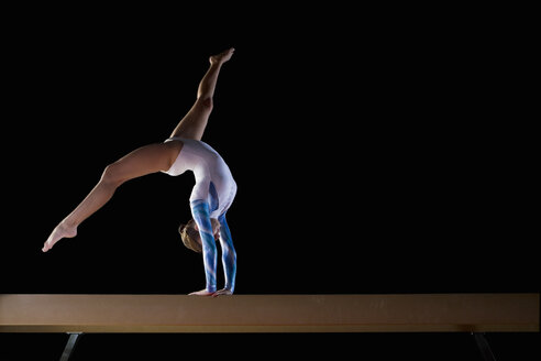 Female gymnast performing on balance beam, low angle view - JUIF00255