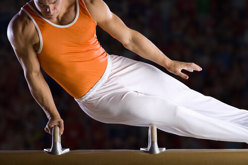 Male gymnast performing on pommel horse, mid section - JUIF00273