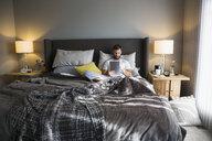 Man using digital tablet in bed - HEROF31113