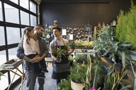 Male shop owner helping father and daughter shopping in plant shop - HEROF31164