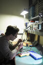 Male electronics engineer working at workbench in workshop - HEROF31179