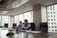 Male lawyers working at laptop in conference room meeting - HEROF31245