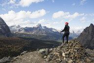 Mountain hiker on pile of rocks looking at mountain view, Lake O - HEROF31278