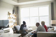Financial advisor with paperwork meeting with senior couple in living room - HEROF31287