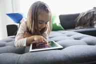 Girl using digital tablet on living room chaise sofa - HEROF31296