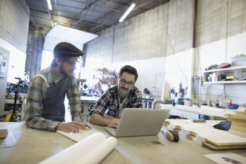 Male carpenters working brainstorming at laptop in workshop - HEROF31326