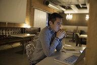 Focused businessman working late at laptop in office - HEROF31380