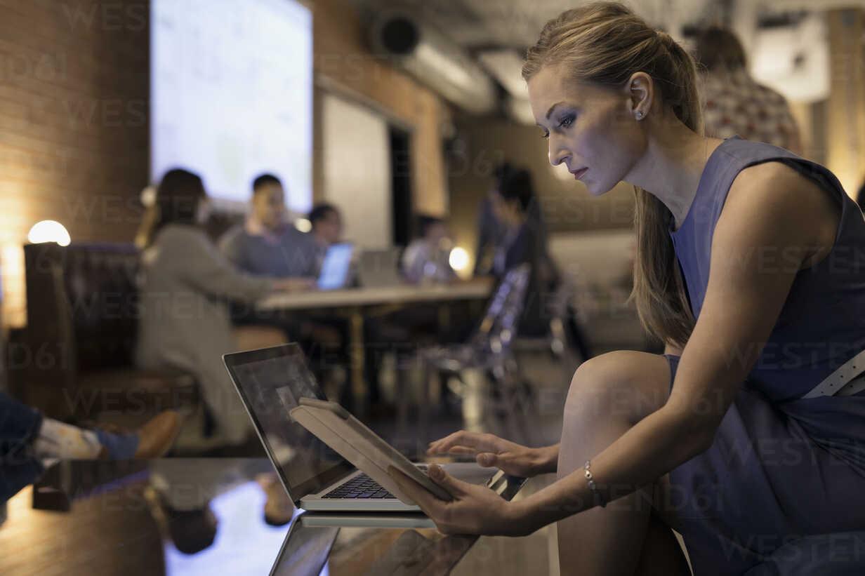 Focused businesswoman working at digital tablet and laptop in office - HEROF31407 - Hero Images/Westend61