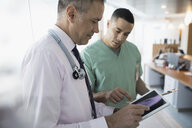 Male doctor and nurse viewing digital x-ray on digital tablet in clinic - HEROF31428