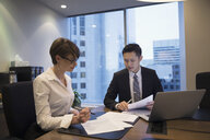 Lawyers reviewing contract at laptop in conference room meeting - HEROF31461