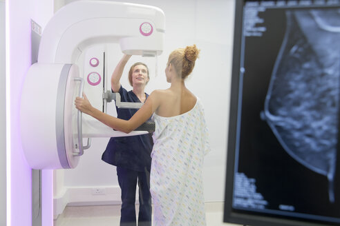 Hospital Radiographer Giving Mammogram To Female Patient - JUIF00318