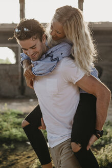 Happy young man giving girlfriend a piggyback ride in an old hall - LHPF00493