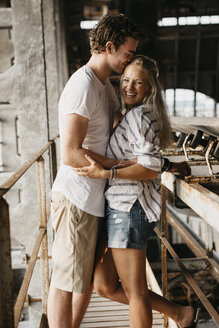 Happy young couple hugging in an old train station - LHPF00511