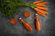 Carrot juice in bottles and glasses, bunch of carrots, from above - LVF07910