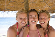Teenage girls posing under beach umbrella - JUIF00386