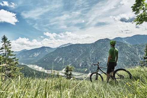Germany, Bavaria, Isar Valley, Karwendel Mountains, mountainbiker on a trip having a break on alpine meadow - WFF00073