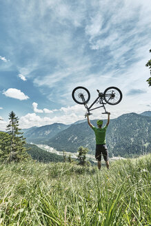 Germany, Bavaria, Isar Valley, Karwendel Mountains, mountainbiker on a trip lifting up his bike on alpine meadow - WFF00076