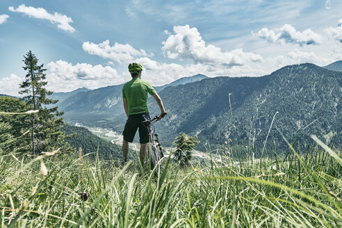 Germany, Bavaria, Isar Valley, Karwendel Mountains, mountainbiker on a trip having a break on alpine meadow - WFF00079