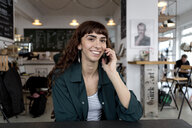 Smiling young woman on cell phone in a cafe - FLLF00071