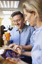 Smiling woman and man using tablet in a cafe - PNEF01392