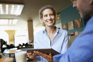 Smiling woman and man with tablet in a cafe - PNEF01395