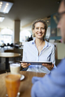 Smiling woman and man with tablet in a cafe - PNEF01398