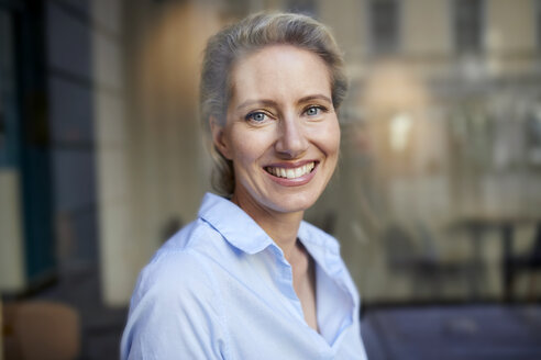 Portrait of smiling woman behind windowpane - PNEF01404