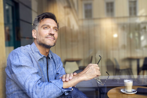 Portrait of man behind windowpane in a cafe - PNEF01407