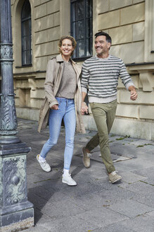 Happy couple walking on pavement in the city - PNEF01422