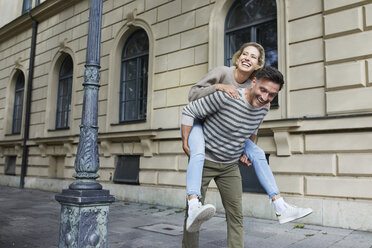Happy man giving woman piggyback ride on pavement in the city - PNEF01425