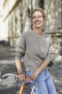 Portrait of happy woman with bicycle in the city - PNEF01428