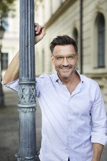 Portrait of smiling businessman leaning against lamp post in the city - PNEF01437