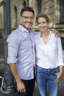 Portrait of happy couple embracing in the city - PNEF01440