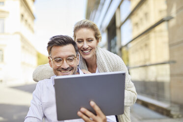 Happy couple using tablet in the city - PNEF01449