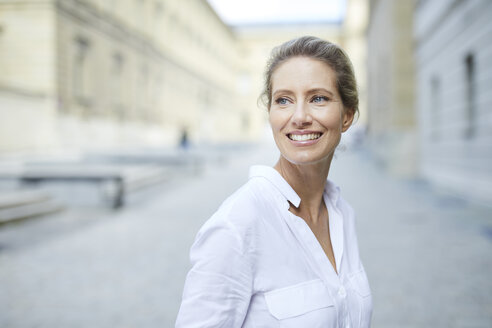 Portrait of smiling woman wearing white shirt in the city - PNEF01455
