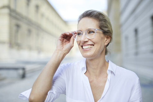Portrait of smiling woman wearing white shirt and glasses in the city - PNEF01458