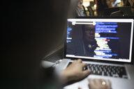 Reflection of female hacker coding working hackathon at laptop - HEROF31535