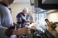 Senior friends cooking and drinking wine in kitchen - HEROF31559