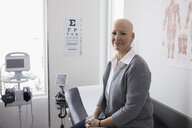 Portrait smiling, confident bald female cancer patient waiting in clinic examination room - HEROF31646