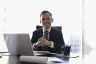 Portrait smiling lawyer working at laptop in conference room - HEROF31652