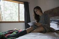 Woman relaxing on bed using digital tablet - HEROF31681