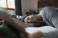 Smiling woman laying on bed using digital tablet - HEROF31684