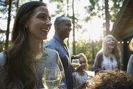 Smiling woman drinking wine at party on cabin balcony - HEROF31690