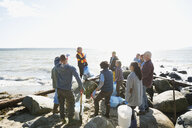 Woman leading beach cleanup volunteers on sunny beach rocks - HEROF31717