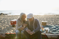 Smiling senior couple enjoying picnic on sunset beach - HEROF31720