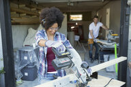 Woman using table saw for home improvement project outside garage - HEROF31756