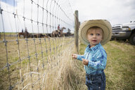 Toddler boy in cowboy hat at fence on ranch - HEROF31765