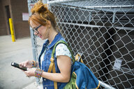 Young woman texting with cell phone in alley - HEROF31768