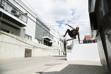 Young man doing parkour free running in sunny urban alley - HEROF31771