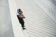 Young man listening to headphones on urban pavement - HEROF31774